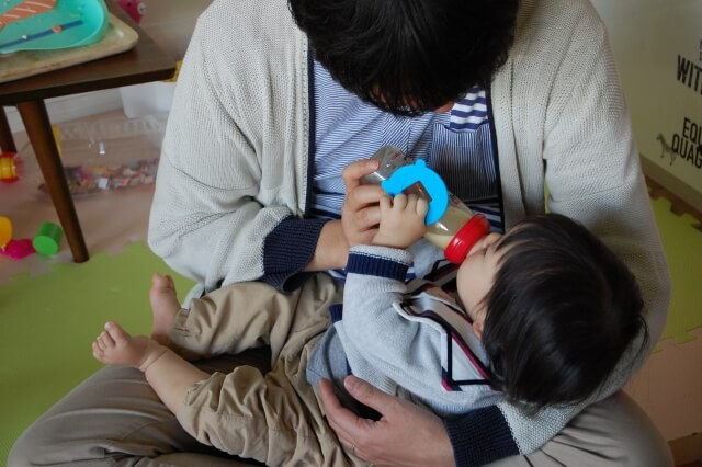 image of a father feeding his baby